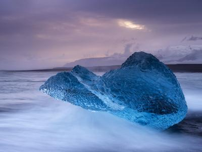 Translucent Blue Iceberg Washed Ashore on Breidamerkursandur Black Sands