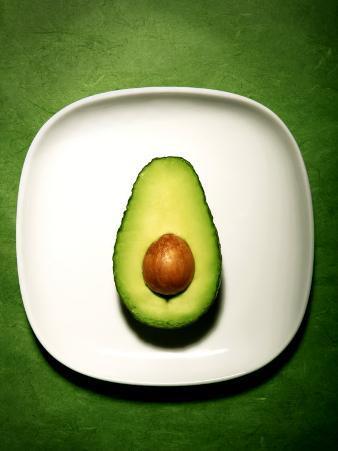 Half an Avocado on a White Plate