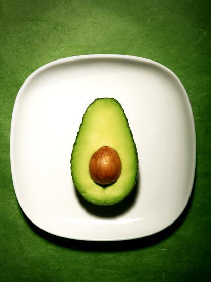Half An Avocado On A White Plate Photographic Print By