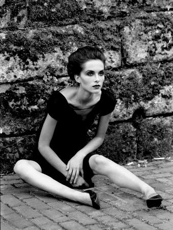 Portrait of a Young Woman in a Dress Sitting on the Ground