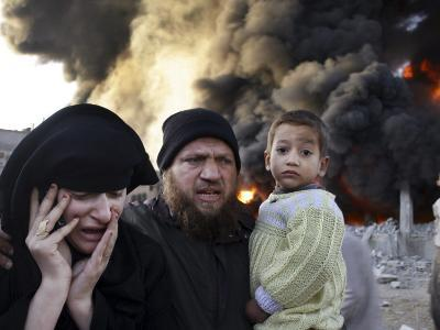 Palestinian Family Rushing Past a Burning Building after an Israeli Missile Strike in the Southern