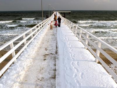 Tourists Walk on the Snow Covered Sea Bridge Pier in a North German Baltic Sea Resort