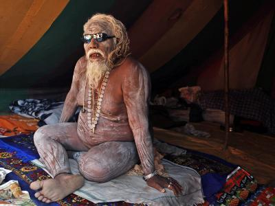 Naked Hindu Holy Man Sits Inside on the Banks of the River Ganges During the Kumbh Mela in India