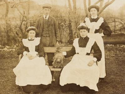 Maids and 'Boy' Pose in their Uniform with the Family Dog