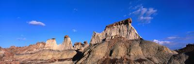 Clouds drift past capped towers of rock, Bisti Wilderness Area, New Mexico