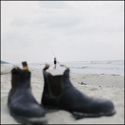Close-Up of a Pair of Boots with a Man Fishing on the Beach in the Background, Sweden