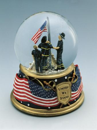 Close-Up of Figurines of Firefighters Standing Near a Flag in a Snow Globe