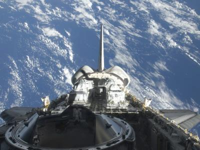A Partial View of Space Shuttle Atlantis Backdropped by a Blue and White Earth