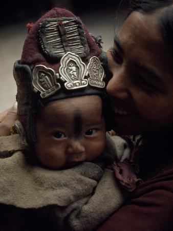 A Baby Wears a Protective Woolen Cap Adorned with Amulets and Needles