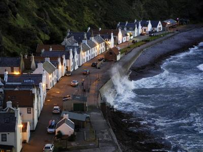 Waves Crash Along the Shoreline in Pennan at Twilight