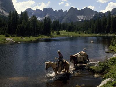 A Guide Leads a Pack String across the North Popo Agie River, Below Cirque of the Towers Peaks