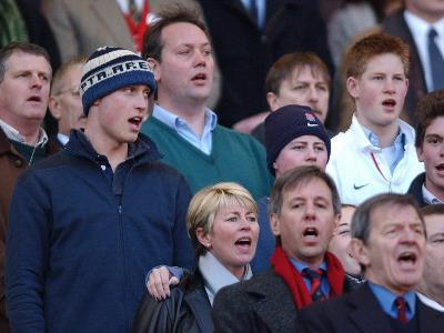 Prince William sings the National Anthem still wearing his wooly hat while his brother Harry does t