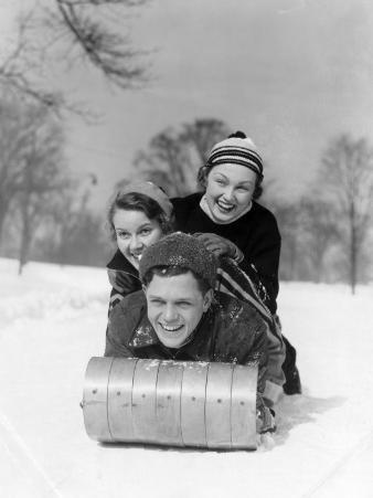 Man and Two Women Wearing Wool Hats and Winter Clothing Tobogganing in Snow