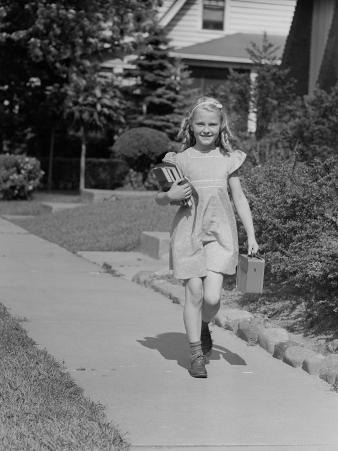 Portrait of Young Girl (8-9) With Lunch Box on Sidewalk