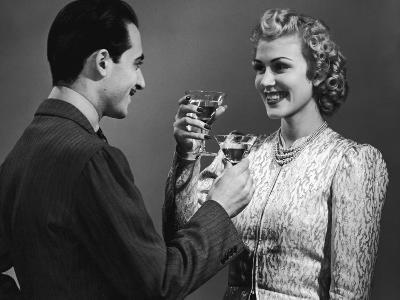Couple Toasting With Cocktails, Circa 1930's