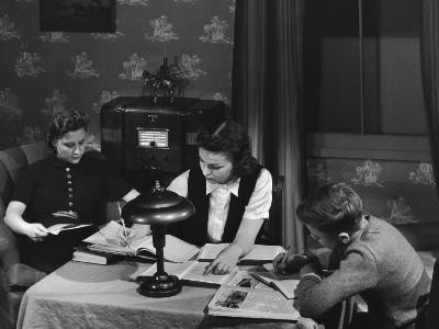 Teenage Children Doing Homework, Mother Sitting Reading in Chair