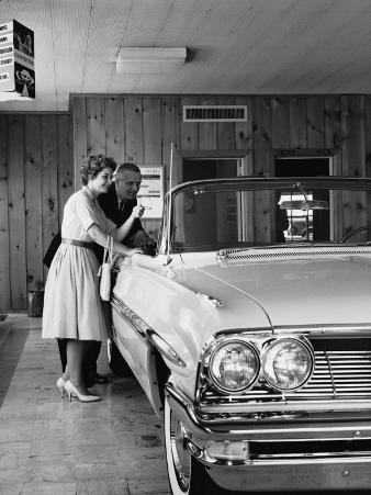 Couple Looking at Convertible in Showroom