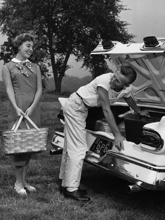 Young Couple Loading Trunk of Car For Picnic