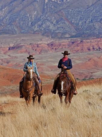 Cowboy and Cowgirl Riding Through Scenic Hills of the Big Horn Mountains, Shell, Wyoming, USA