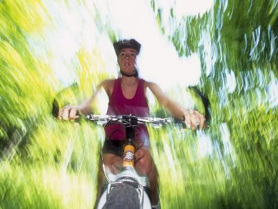 Young Female Recreational Mountain Biker Riding in the Forest