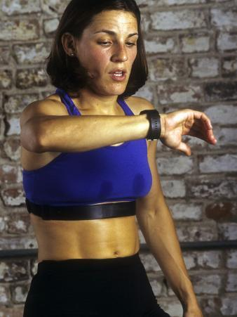 Young Woman Exercising on a Stationary Bike Checking her Heart Rate