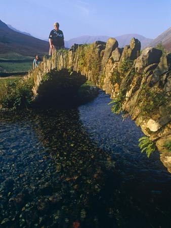 Eskdale, Cumbria, Walkers Crossiing a Tradition Stone Bridge