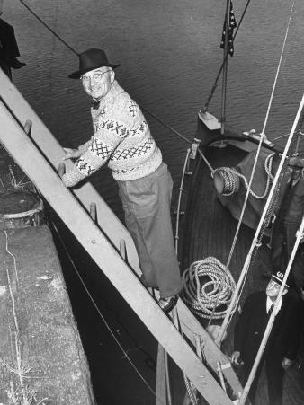 President Harry S. Truman Standing on a Ladder Between a Dock and a Boat