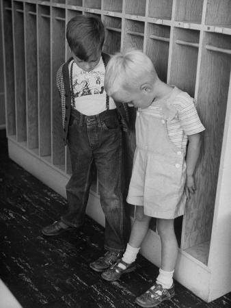 Two Little Boys Comparing the Size of their Feet in Kindergarten Class