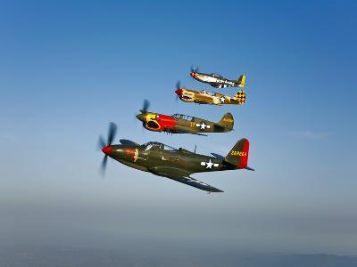 A P-36 Kingcobra, Two Curtiss P-40N Warhawks, and a P-51D Mustang in Flight