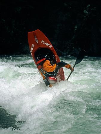 A Kayaker Paddles in Waves on the Kananskis River, Near Calgary