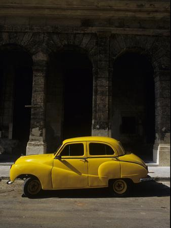 An Old Yellow Car Sits at the Curb in Old Havana