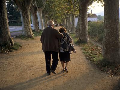 An Elderly Couple Walking Along a Tree-Lined Dirt Road