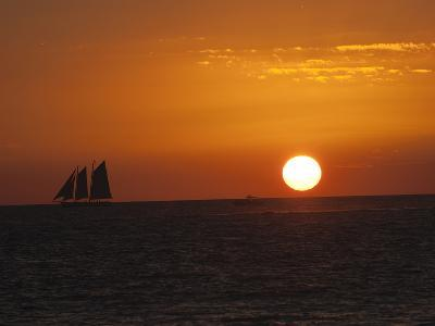 A Boat Sails across the Horizon at Sunset