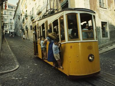 High Quarter Jam-Packed Cable Trolly Descends a Cobblestoned Street