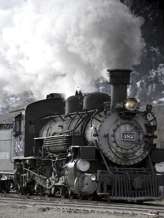 A Steam Train Puffing Smoke While Moving Down Tracks