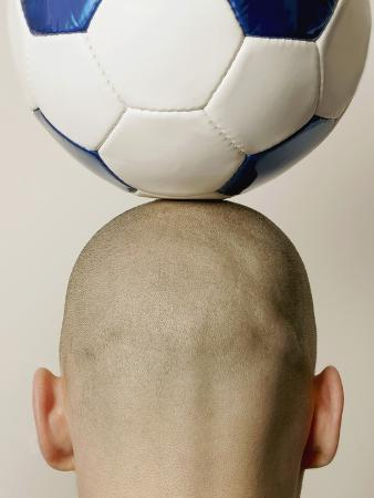 Man with soccer ball on head, rear view, close-up