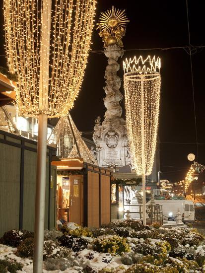 snow covered flowers christmas decorations and baroque trinity column at christmas market austria - Christmas Column Decorations