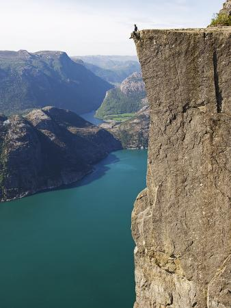 Man Sitting on Preikestolen (Pulpit Rock) Above Fjord, Lysefjord, Norway, Scandinavia, Europe