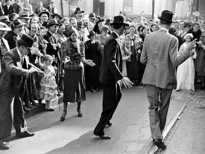 Men dancing in the street as revelers celebrate New Orleans Mardi Gras. February 1938