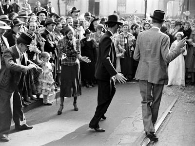 Men dancing in the street as revelers celebrate New Orleans Mardi Gras. February 1938