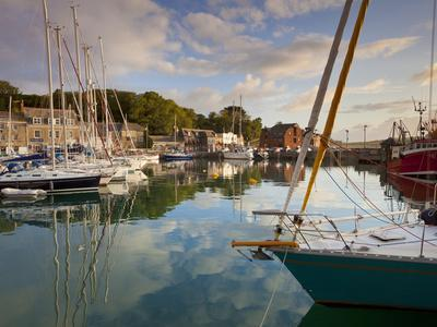 Low Morning Light and Sailing Yacht Reflections at Padstow Harbour, Cornwall, England, United Kingd