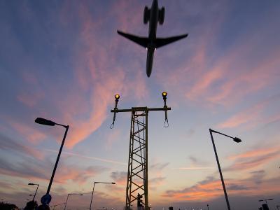 Dc9 Aircraft Approaching over Runway Landing Light Gantries at Sunset, London, England, United King
