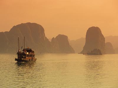 Traditional Boat Sailing Through Limestone Archipelago at Sunset, Ha Long Bay, UNESCO World Heritag