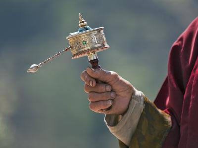 A Buddhist Spins His Hand-Held Prayer Wheel in a Clockwise Direction with the Help of a Weighted Ch