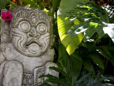 Bali, Ubud, a Stone Carving, Adorned with a Hibiscus Flower, Sits in Tropical Gardens
