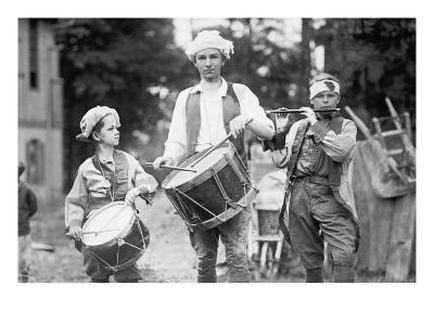 Three Boys March with Instruments on the 4th of July Celebration