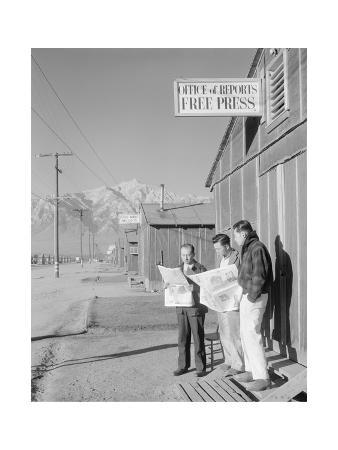 Roy Takeno (Editor) and Group Reading Manzanar Paper [I.E. Los Angeles Times] in Front of Office