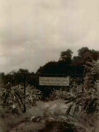 Front Gate Welcome Sign and Gate at the Beginning of the Road into Jonestown