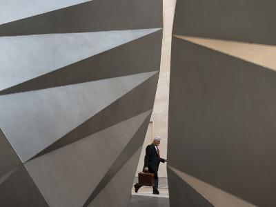 A Businessman Walks Past a Sculpture in the Middle of London