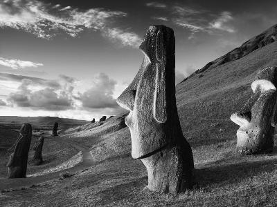 A Path Winds Past Moai Spread across Rolling Hills